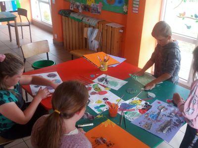Zdjęcie przedstawia grupkę dzieci z PWD Laski podczas wykonywania prac plastycznych.
