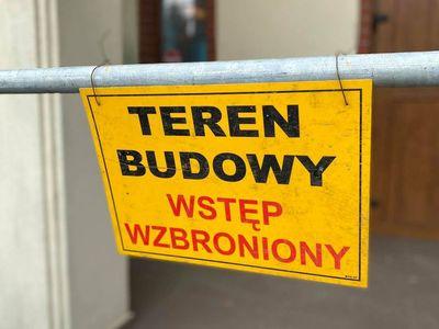 Zdjęcie przedstawia tabliczkę z napisem Teren Budowy Wstęp Wzbroniony przed modernizowanym domem przedpogrzebowym w Malechowie.