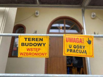 Zdjęcie przedstawia tabliczkę z napisem Teren Budowy Wstęp Wzbroniony oraz Uwaga! U góry pracują, które znajdują się przed modernizowanym domem przedpogrzebowym w Malechowie.