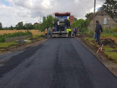 Zdjęcie przedstawia remontowany odcinek drogi w Malechówku, osoby zaangażowane w pracę oraz specjalistyczną maszynę od utwardzania nawierzchni.