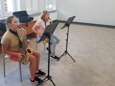 Zdjęcie przedstawia dwie uczennice podczas próby gry na saksofonie w Świetlicy Kultury w Malechowie.