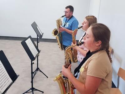 Zdjęcie przedstawia dwie uczennice z instruktorem grających na saksofonie w Świetlicy Kultury w Malechowie.
