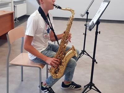 Zdjęcie przedstawia chłopca grającego na saksofonie podczas próby w Świetlicy Kultury w Malechowie.