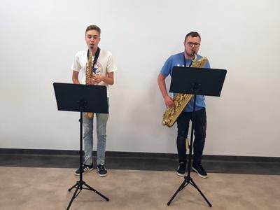 Zdjęcie przedstawia chłopca wraz instruktorem grających na saksofonie podczas próby w Świetlicy Kultury w Malechowie.