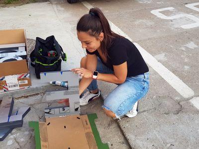 Zdjęcie przedstawia kobietę podczas przygotowania liter do montażu napisu Świetlica Kultury w Malechowie.