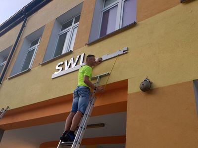 Zdjęcie przedstawia montaż napisu Świetlica Kultury w Malechowie na początkowym etapie oraz mężczyznę na drabinie.