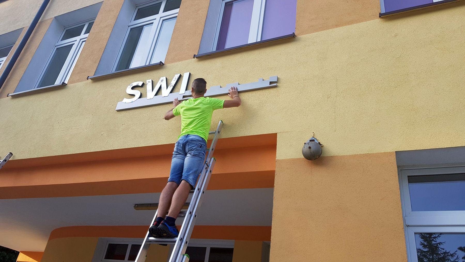 Zdjęcie przedstawia montaż napisu Świetlica Kultury w Malechowie, mężczyznę na drabinie podczas prac montażowych.