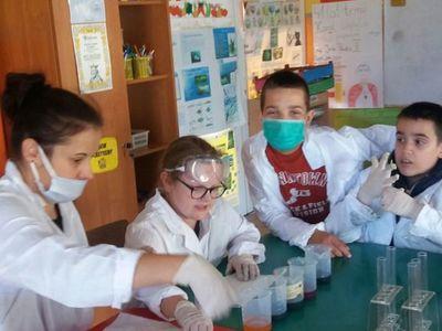 Zdjęcie przedstawia dzieci z PWD w Laskach uczestniczących w zajęciach fizyczno-chemicznych z elementami matematyki podczas przygotowywania doświadczenia.