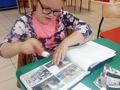Zdjęcie przedstawia wychowankę z PWD z Lasek, która przykleja zdjęcia do kroniki.