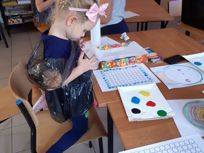 Zdjęcie przedstawia dziewczynkę podczas malowania paluszkami i farbami oraz pozostałe podopieczne PWD Paproty w tle.