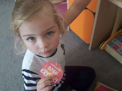 """Zdjęcie przedstawia dziewczynkę z przedszkola w Niemicy pozującą z odznaką """"Międzynarodowy Dzień Kropki""""."""