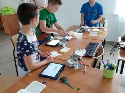 Zdjęcie przedstawia wychowanków PWD Przystawy podczas zajęć z robotyki ze składanymi przez nich robotami.
