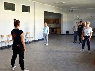 Zdjęcie przedstawia ćwiczenia ruchowe seniorów z Malechowa, które gimnastykują się pod okiem fizjoterapeuty.