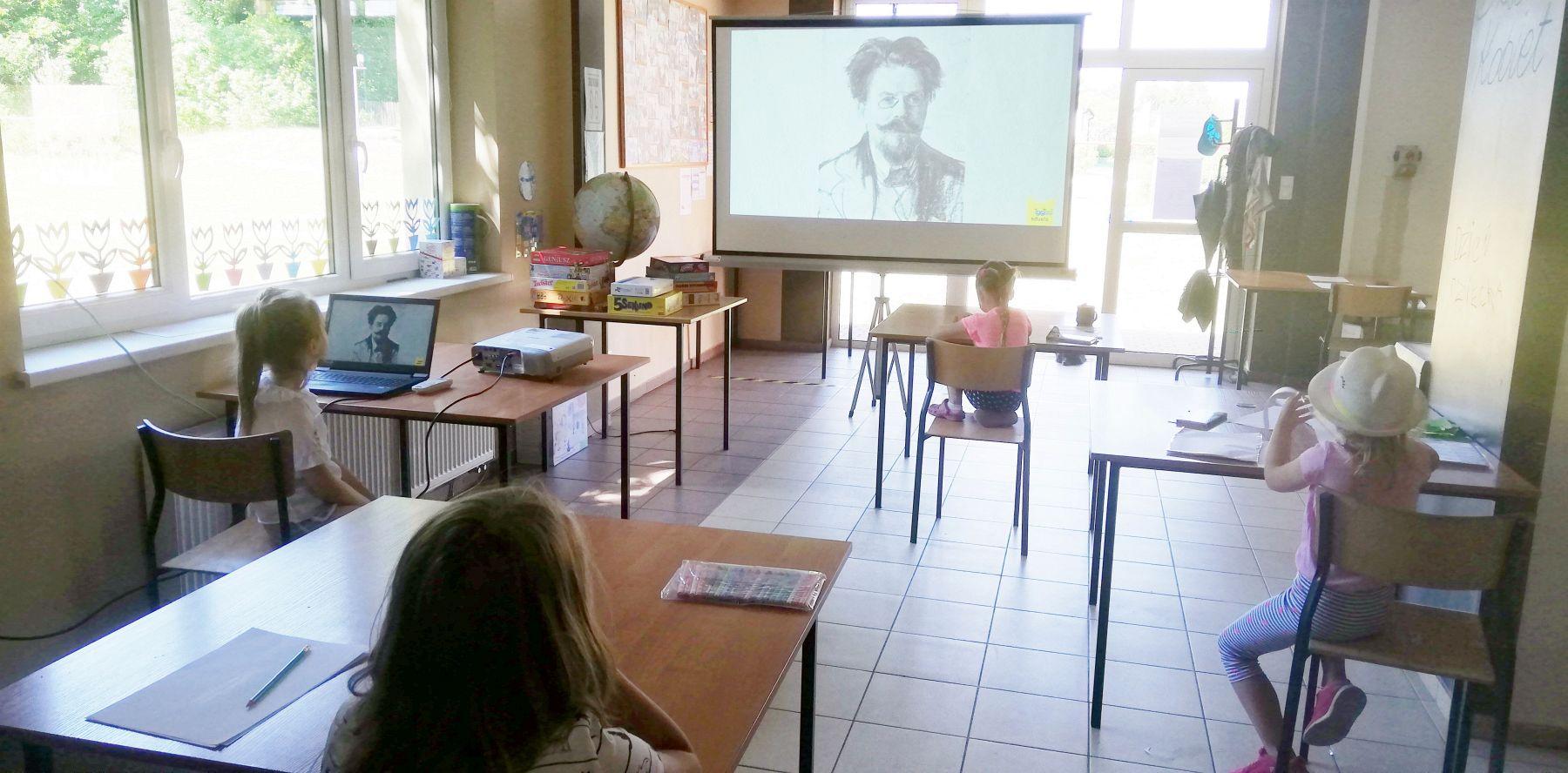 Zdjęcie przedstawia dzieci z Pwd w Sulechowie oglądające prezentację multimedialną podczas zajęć dziennikarskich.