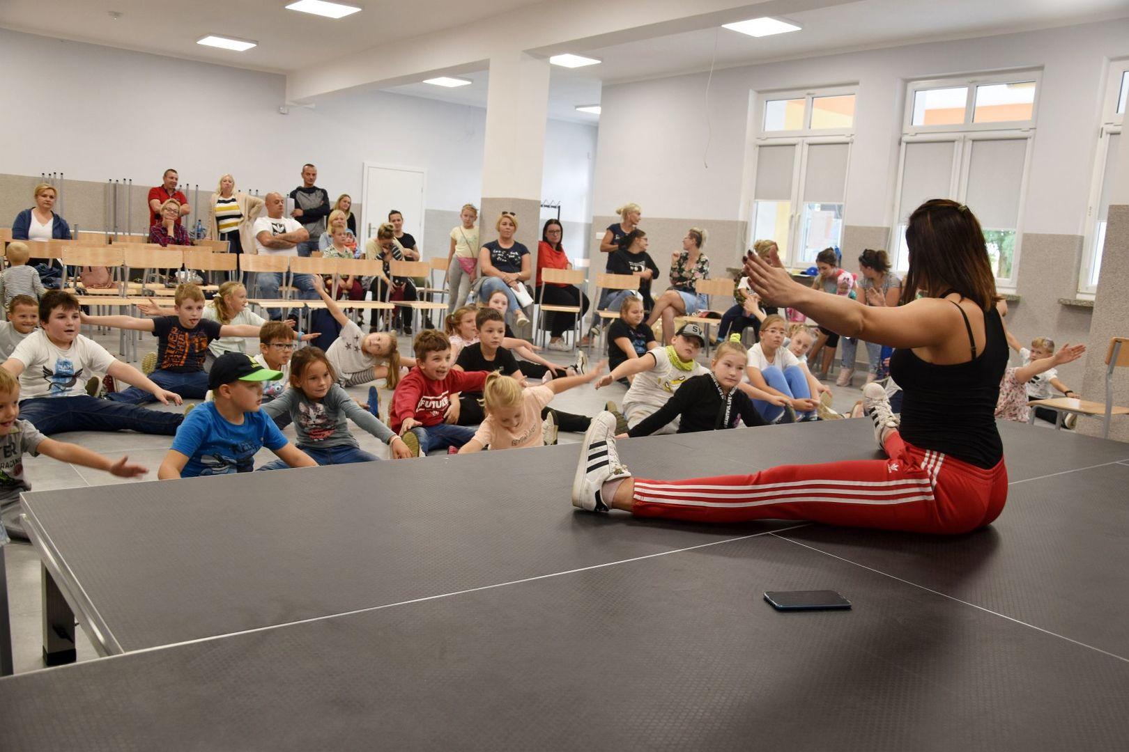 Zdjęcie przedstawia zajęcia pokazowe breakdance w Świetlicy Kultury w Malechowie: instruktorkę oraz dzieci biorące udział w lekcji pokazowej.