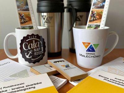Zdjęcie przedstawia pakiety promocyjne Gminy Malechowo jako nagrody w Konkursie Fotograficznym InstaMalechowo 2020.