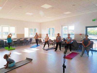 Zdjęcie przedstawia seniorów z Ostrowca podczas ćwiczeń ruchowych w Domu Wiejskim w Ostrowcu.