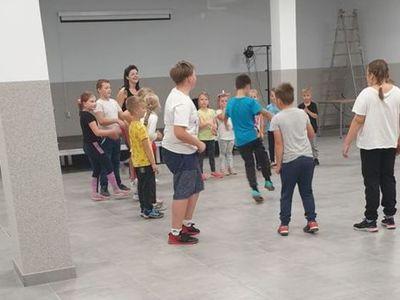 Zdjęcie przedstawia dzieci uczestniczące w zajęciach breakdance w Świetlicy Kultury w Malechowie wraz z instruktorką.