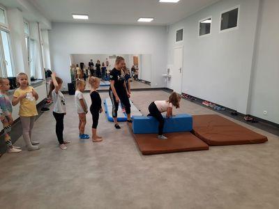 Zdjęcie przestawia dzieci uczestniczące w zajęciach akrobatyki i tańca z trenerką, podczas wykonywania ćwiczenia w sali tanecznej Świetlicy Kultury w Malechowie.