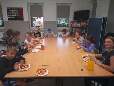 Zdjęcie przedstawia dzieci podczas jedzenia pizzerek.