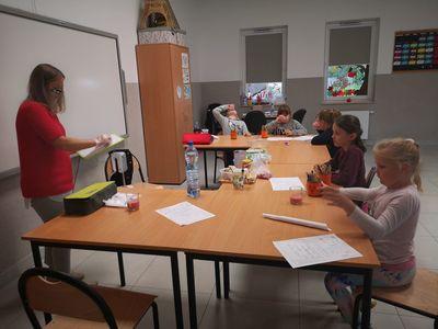 Zdjęcie przedstawia prowadzącą i grupę dzieci podczas nauki nazw owoców z j. angielskiego.