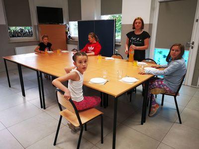 Grupę dzieci z PWD Kusice rozkładająca talerze na stół.