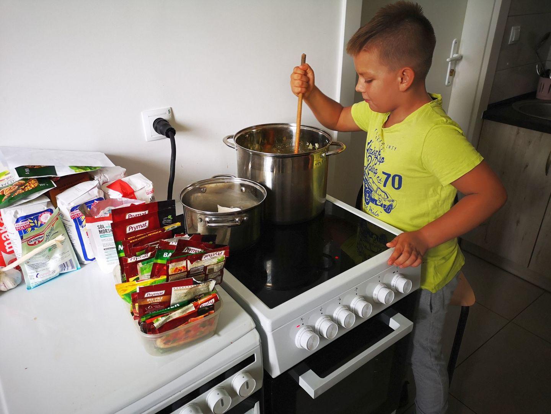 Wychowanek placówki z Kusic podczas gotowania potrawy.