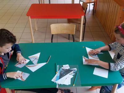Wychowankowie PWD Laski układający zegary z elementów.