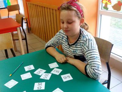 Dziecko z PWD Laski grające w grę polegającą na odnalezieniu par zegarów analogowy - elektroniczny, wskazujących tę samą godzinę.