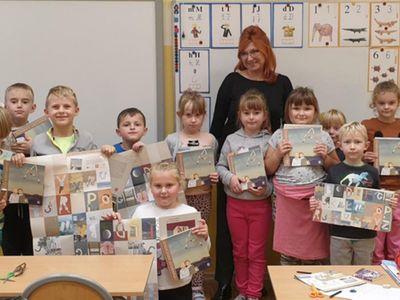 Uczniowie klasy I ze Szkoły Podstawowej w Niemicy razem z wychowawcą demonstrują swoje prezenty w postaci książek i kreatywnego alfabetu.