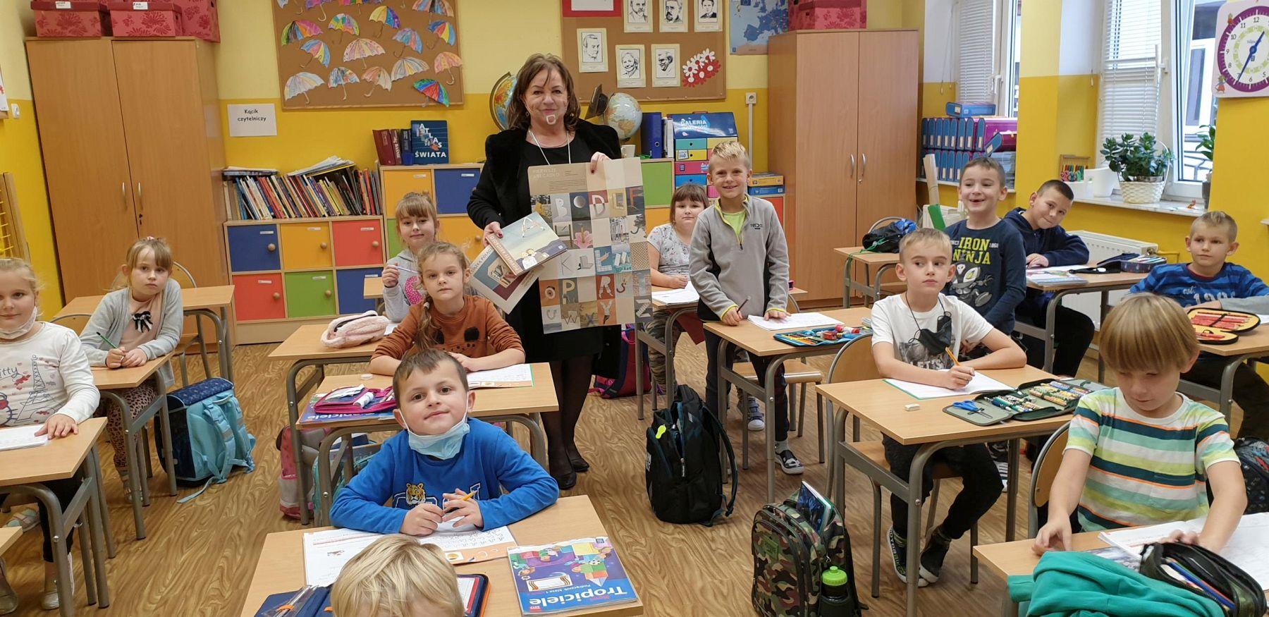Dyrektor SP Niemica - Iwona Nowak-Gancarz prezentuje uczniom klasy I Wyprawkę Czytelniczą.