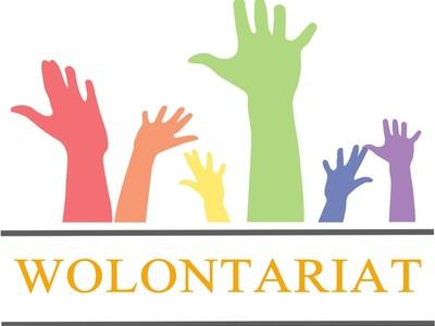 Kolorowe dłonie uniesione w górę i napis wolontariat