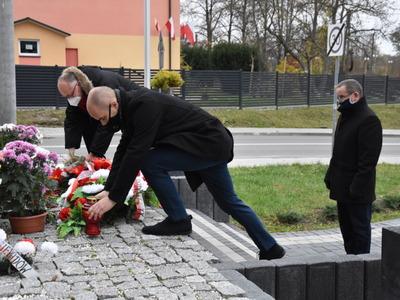 Sekretarz Gminy i Przewodniczący Rady Gminy stawiają zniczy przy pomniku