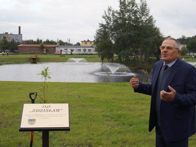 Zdzisław Polek stoi przy pamiątkowej tablicy